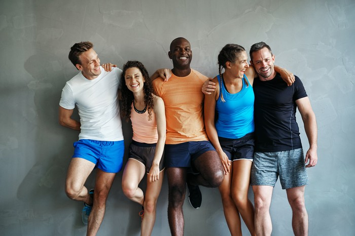 Smiling men and women wearing activewear are standing against a grey wall.