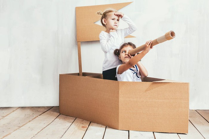 Two little girls playing inside a cardboard box boat, with one seated while looking through a cardboard tube.