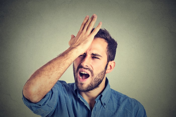 A bearded man smacking his head with his right hand and grimacing.