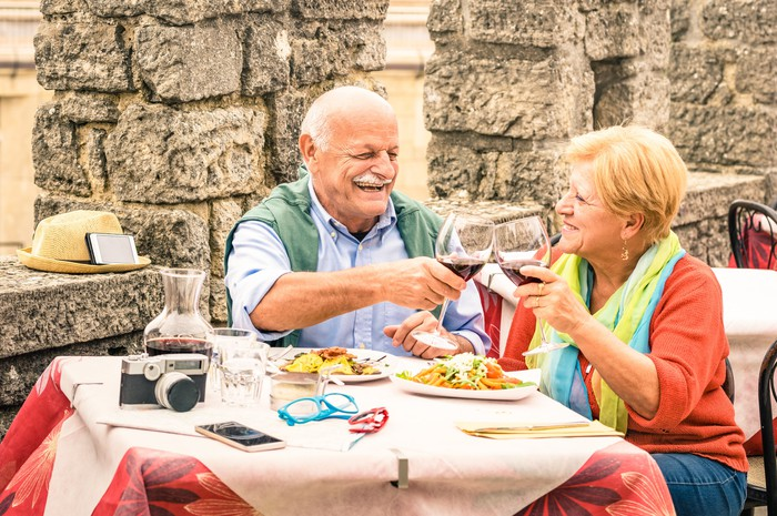 Senior couple dining outdoors, clinking wine glasses