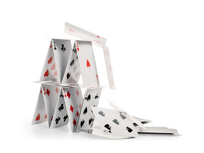 A house built out of playing cards crumbles.