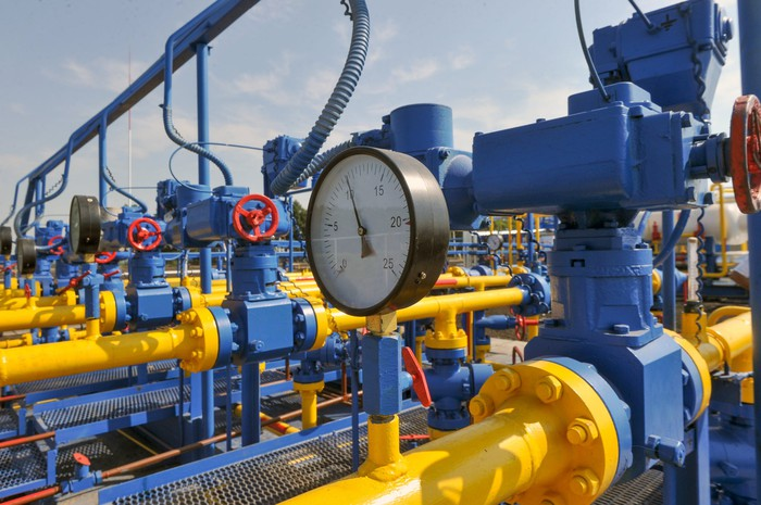 A pressure gauge, pipes, and valves at a natural gas treatment plant.