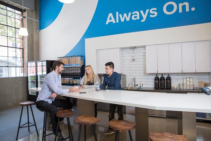 Employees sit around a table in the break room at Okta