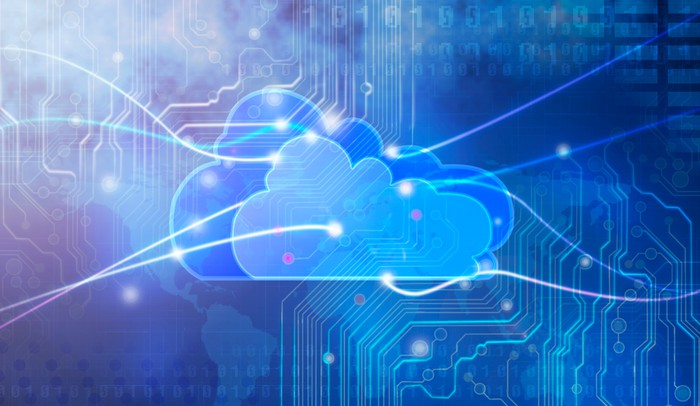 An animation of a cloud, with computer circuits in the background and trails of light extending from the edges of the image to points on the cloud.