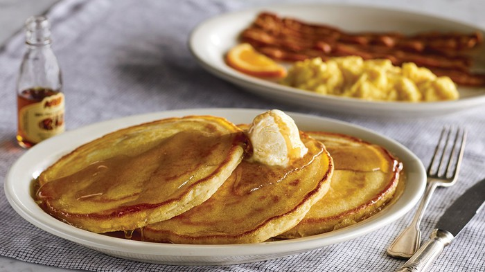 On a tabletop are two plates, One has eggs and bacon, and the other has pancakes with butter and syrup.