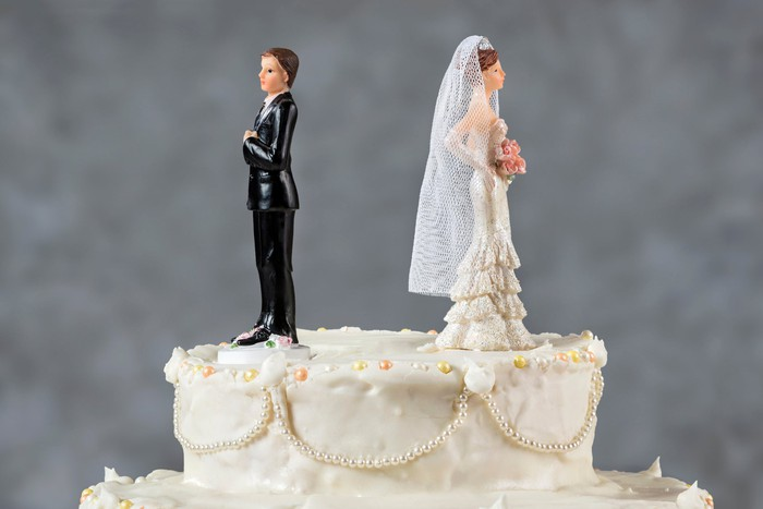 Bride and groom figurines pointed away from each other on top of a wedding cake.