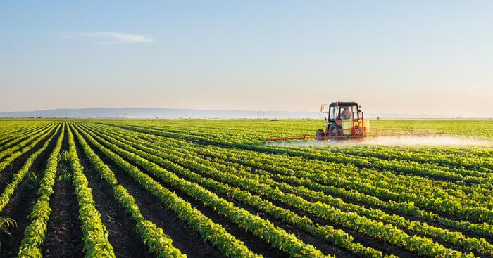 A tractor sprayer on a green farm.