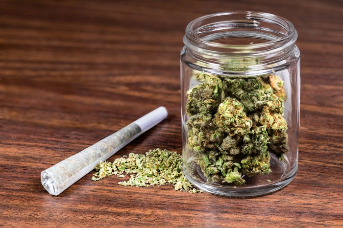 Dried cannabis flowers in a glass jar and a pre-rolled joint sitting on top of a wooden table top.