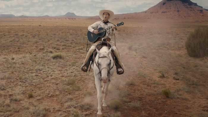 "Still image of a cowboy playing guitar on a horse in the desert from ""The Ballad of Buster Scruggs"""