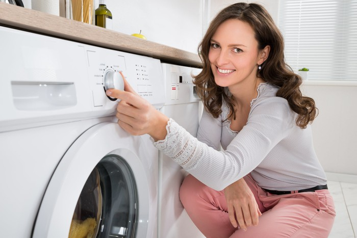 A woman turns on a washer machine.