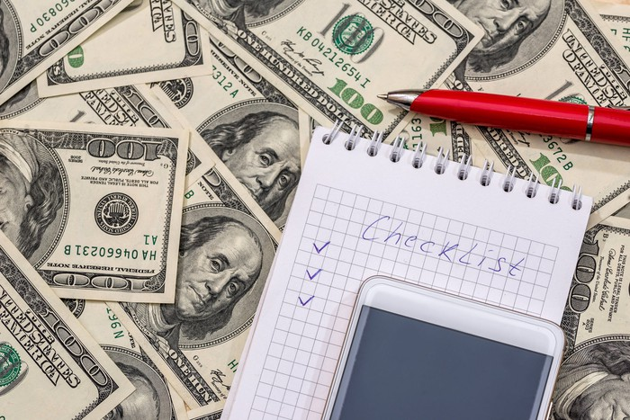 A notebook on top of a pile of $100 bills and the word checklist on it