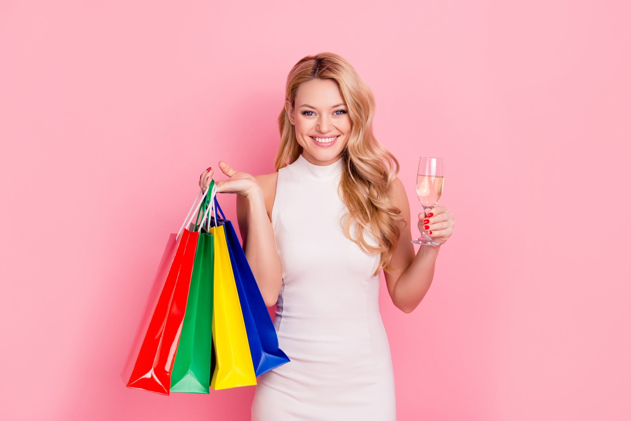 Woman holding shopping bags and wine glass against pink background.