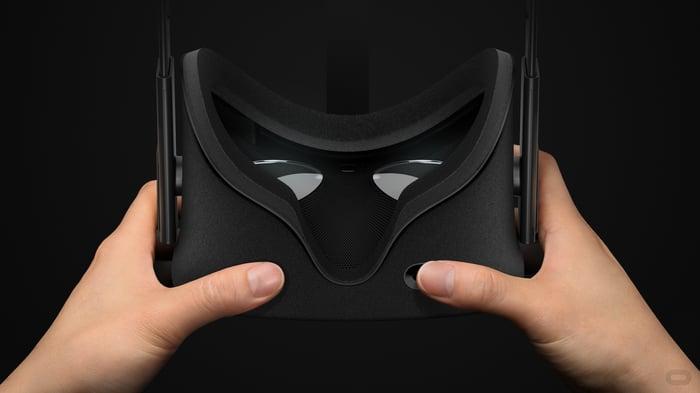 A pair of hands holds an Oculus headset.