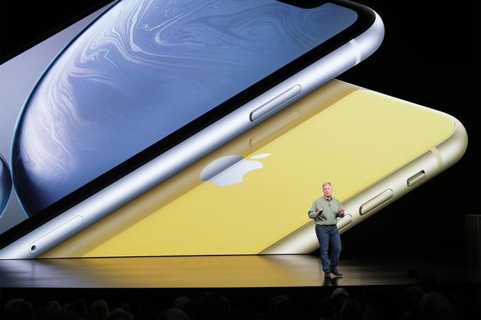 Apple executive Phil Schiller on stage with images of blue and yellow iPhone XRs projected behind him.