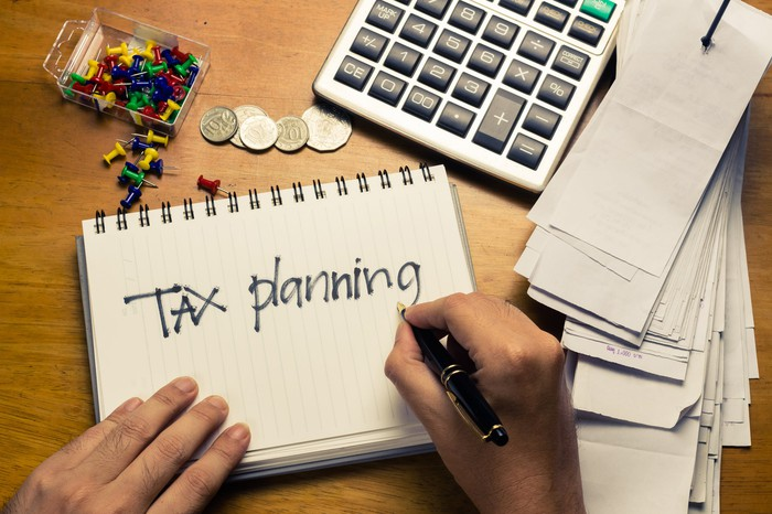 Hands writing tax planning on a notebook that is on a desk along with checks, a calculator, stick pins, and loose change.