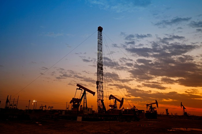 A drilling rig surrounded by oil pumps at sunset.