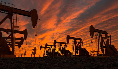 Rows of oil pumps under a twilight sky.