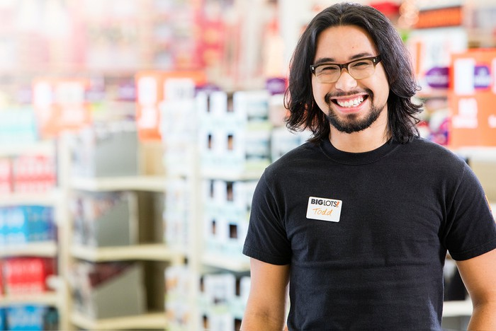A Big Lots employee smiles with merchandise in the backgorund