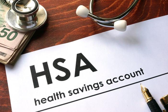 Word HSA written on a paper near wad of bills