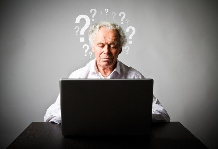 A retiree in front of a laptop computer with question marks on a wall behind him.