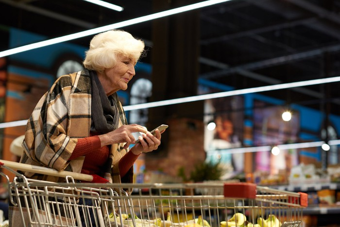 Senior woman typing on phone while pushing shopping cart.