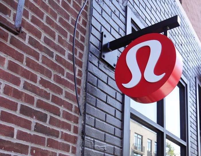 Sign with lululemon logo hanging from post sticking out of a brick wall.