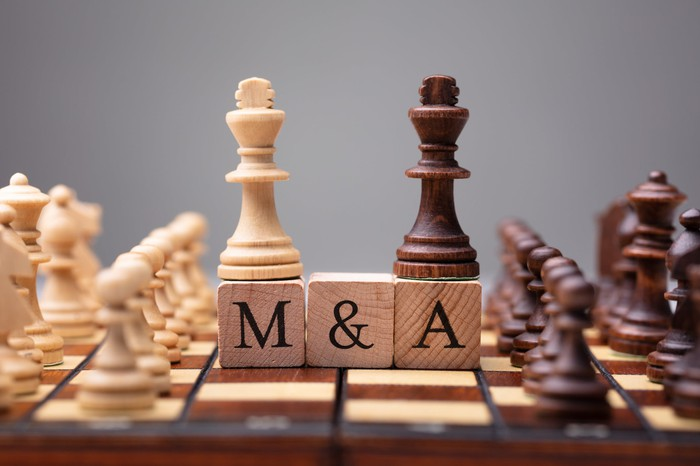 White and black kings placed side-by-side in the middle of a chessboard on top of wood blocks carrying the letters M and A, for mergers and acquisitions.
