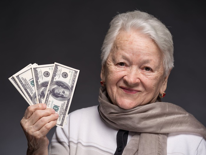 A senior woman holding up a few fanned hundred dollar bills in her right hand.