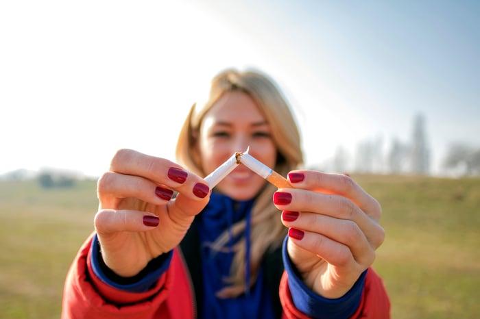 A woman snaps a cigarette in half.