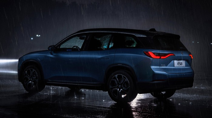A blue NIO ES8 shown driving in heavy rain at night.