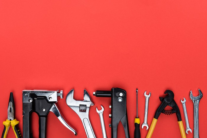 A set of workman's tools lined up against a red background.