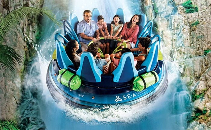 A family of eight in a round water raft going down a waterfall at SeaWorld.