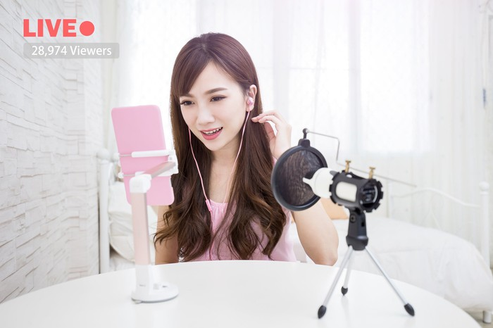 A young social media influencer broadcasts a live video.