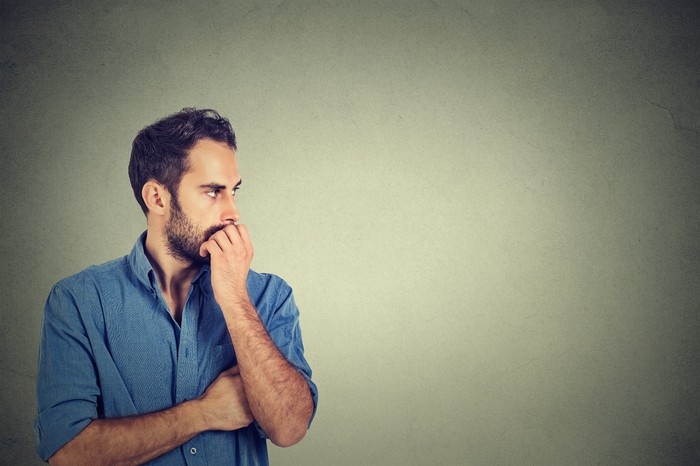 Man holding hand over mouth and looking to his left, seemingly in deep thought.