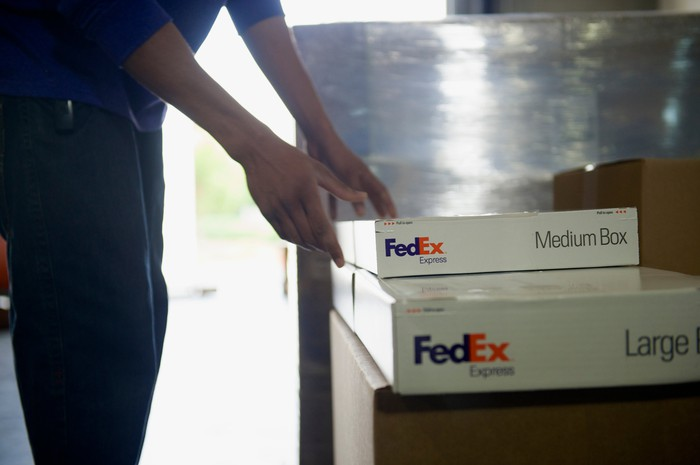 FedEx Express worker arranging a large and a medium box.