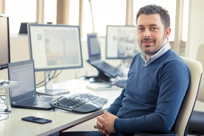 Man sitting at desk smiling with multiple computer screens in the background.