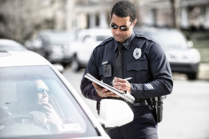 An officer wearing an Axon corpse camera writing a ticket.