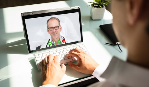 Man typing on keyboard with physician on screen