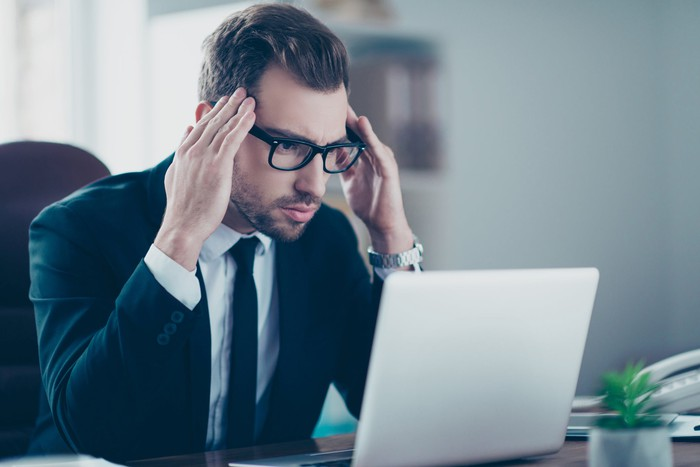Bespectacled man in suit at laptop with annoyed expression, holding the sides of his head