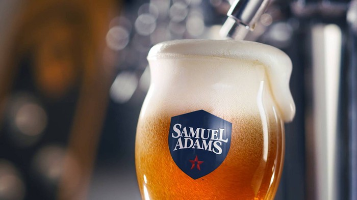 A Samuel Adams beer glass at a tap with foam spilling over