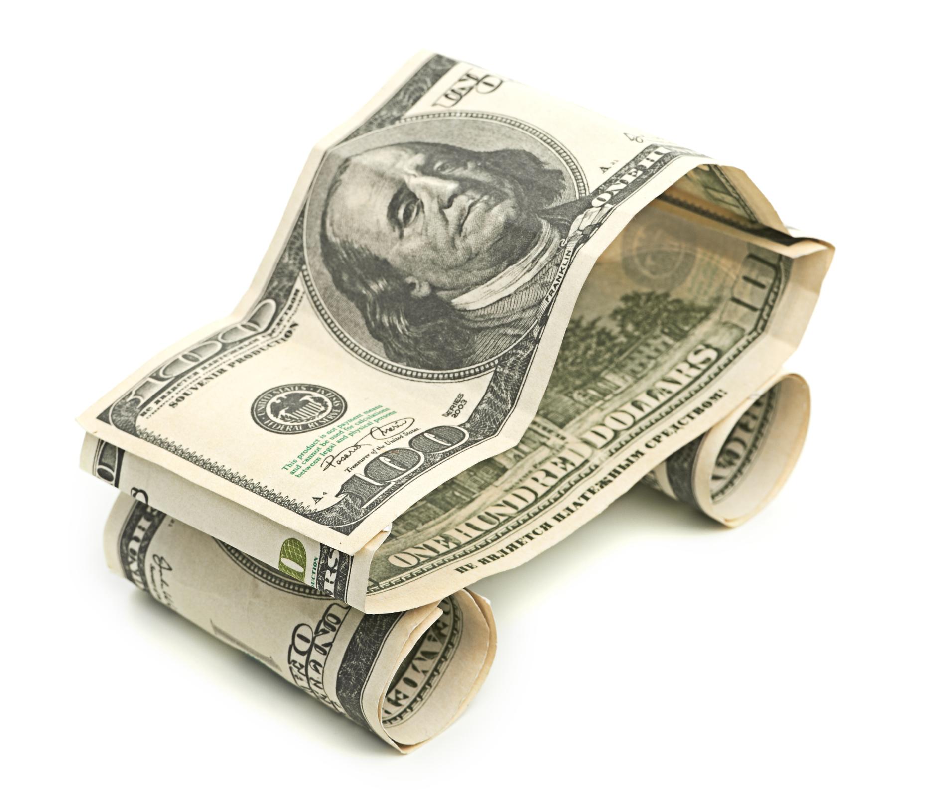 Three hundred-dollar bills folded into a simple car.