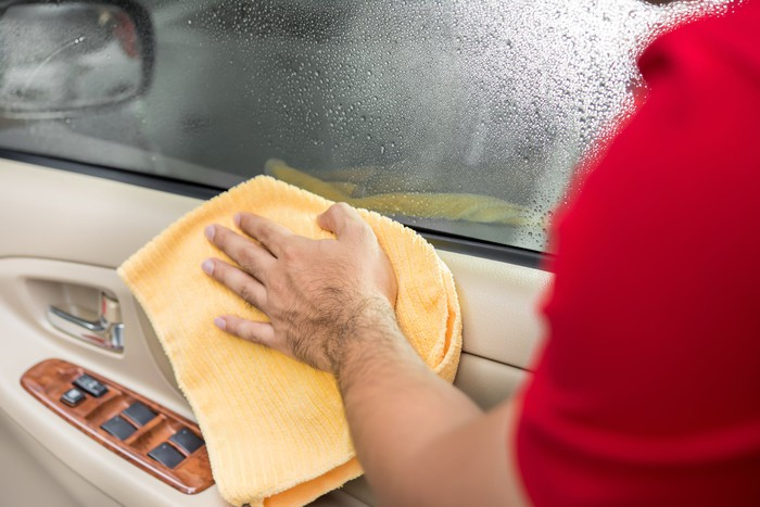 Man cleaning the interior of a car door with a microfiber cloth.