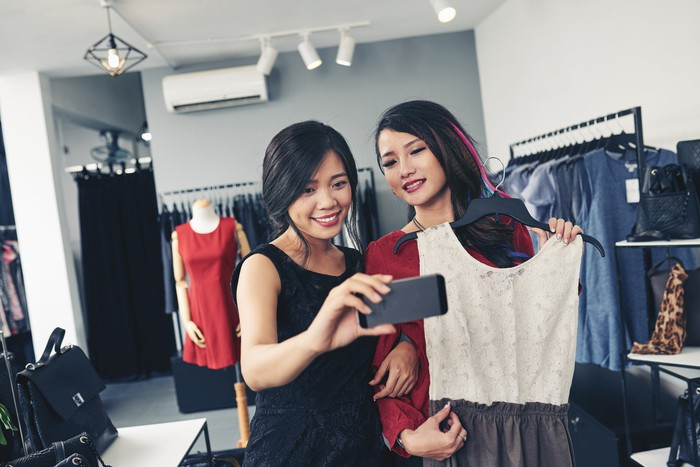 A pair of young women show an outfit to viewers on a smartphone.