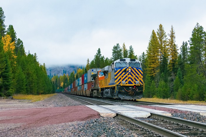 Freight train rolling through valley with green pine trees on either side.