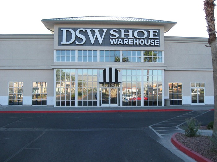 DSW Shoe Warehouse storefront as seen from parking lot, with red curbs and black asphalt.