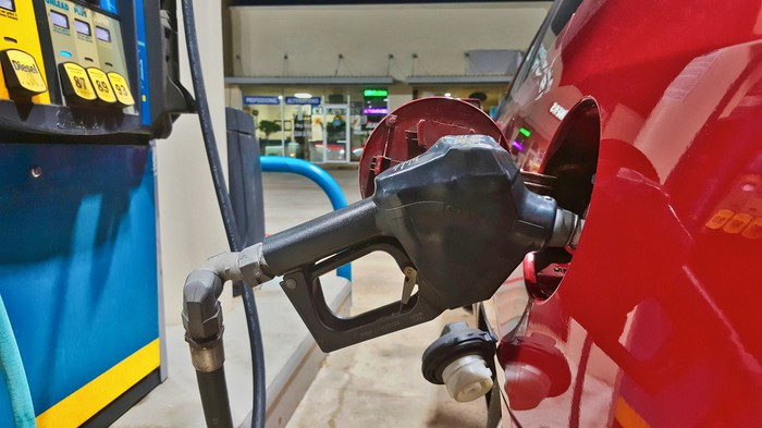 A car filling up with gasoline at a gas station, showing a close-up of the pump in the gas tank from a side view.