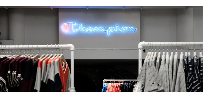 A brightly lit Champion logo on a grey wall inside a store with clothing racks in the foreground.