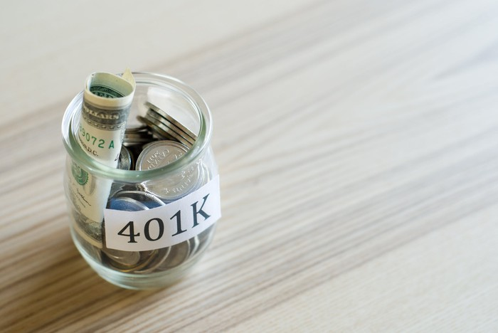 "Glass jar labeled ""401K"" filled with rolled-up bills and coins."