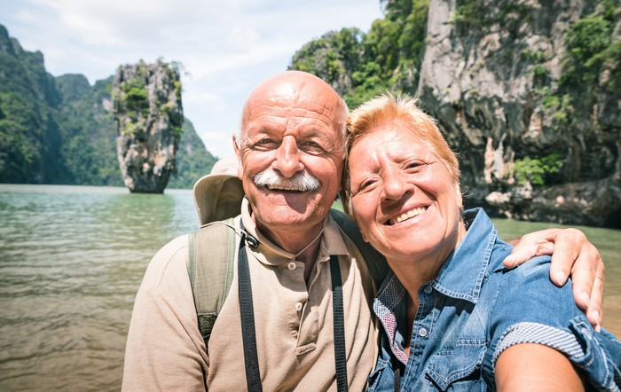 Smiling senior couple out on a body of water
