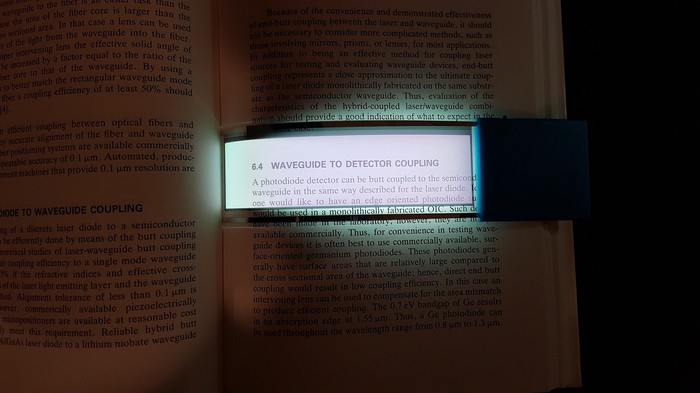 Transparent OLED reading light illuminating a book in the dark